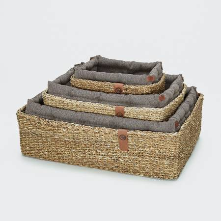 three dog baskets with brown pillows in different sizes
