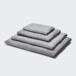 Vier Hundekissen in grauem Tweed-Stoff in verschiedenen Größen mit Griffen übereinandergestapelt