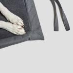 Detailfoto heller Pfoten auf dunkelgrauer Hundematte mit dunklem kuscheligen Innenfutter