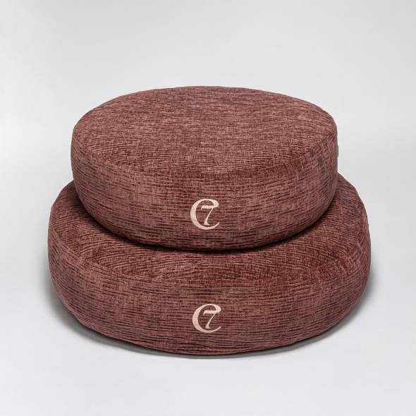 two round dog beds in purple