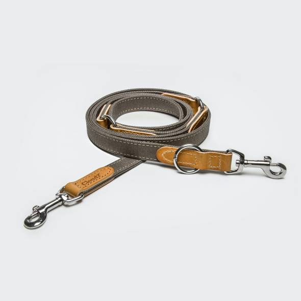 Draped grey canvas dog leash with light brown leather elements and silver closure